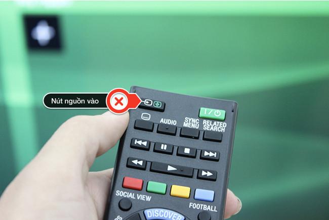 Dùng remote bấm vào nút nguồn vào của TV