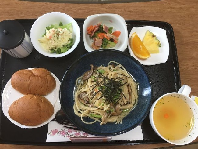 Stir-fried noodles with mushrooms, potato salad, broccoli and bacon salad, chicken soup, fruit, bread and green tea