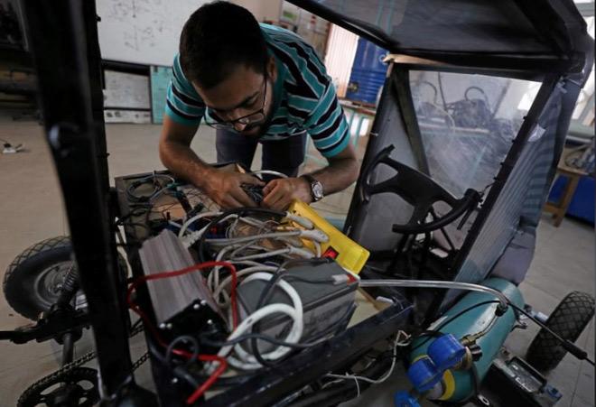 Islam Ibrahim, một sinh viên trong đội ngũ thiết kế đang chỉnh lại các dây cáp điện trên chiếc xe