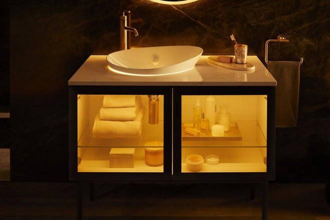 Bồn rửa và một tủ kính bên dưới đựng khăn tắm và mỹ phẩm