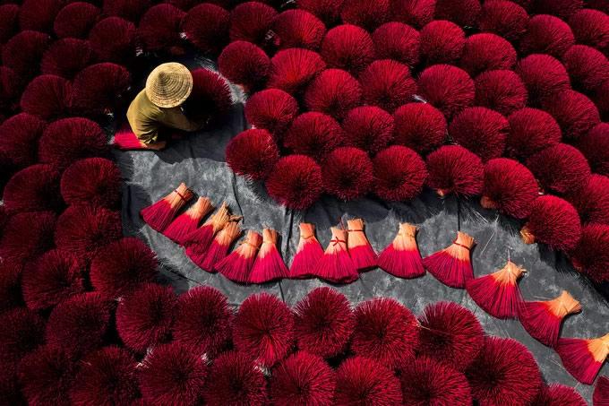 Người phụ nữ phơi những bó hương đỏ rực phủ kín sân