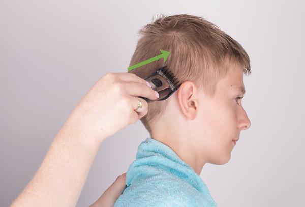 Dùng tăng đơ cắt và cạo ngắn phần tóc 2 bên đầu của bé trai