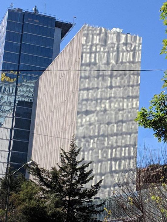 Tòa nhà đối diện trông thật kì dị và khó hiểu hết sức khi được chụp thông qua tấm kính