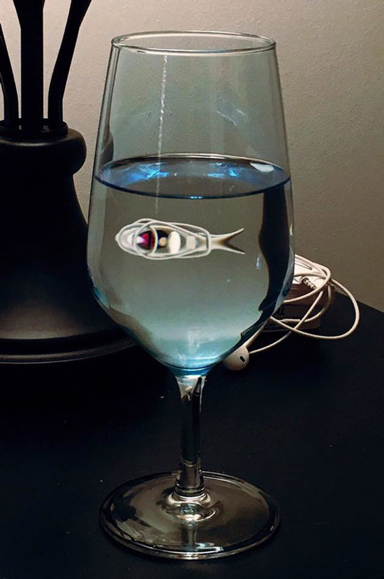 Hình phản chiếu của chiếc tai nghe trên ly nước trông giống như có một con cá trắng đang bơi vậy